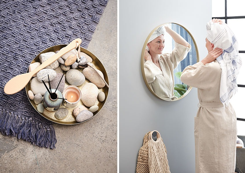Women in bathrobe in front of round mirror and tray with scented oil